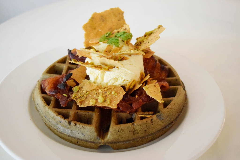 """Squid Ink Waffle with Dijon Maple Bacon ($18.90) Pistachio Tuile, Vanilla Ice-cream Who would pass up bacon? This was easily one of the waffles that I really wanted to try at Waffle Slayer. This was the last waffle served, and it took around 10 minutes after the previous waffle to arrive. (Cranky waffle iron!) Great concept again for waffles, though I did felt that the execution fell flat here. I felt the waffle was quite dry here, which made me think that it was like bread. (My first time associating waffles with bread.) Not much taste was in the waffle as well. The toppings were nice though. I did like the Dijon Maple Bacon. It reminded my friends and I of sweet """"Bak Kwa""""."""