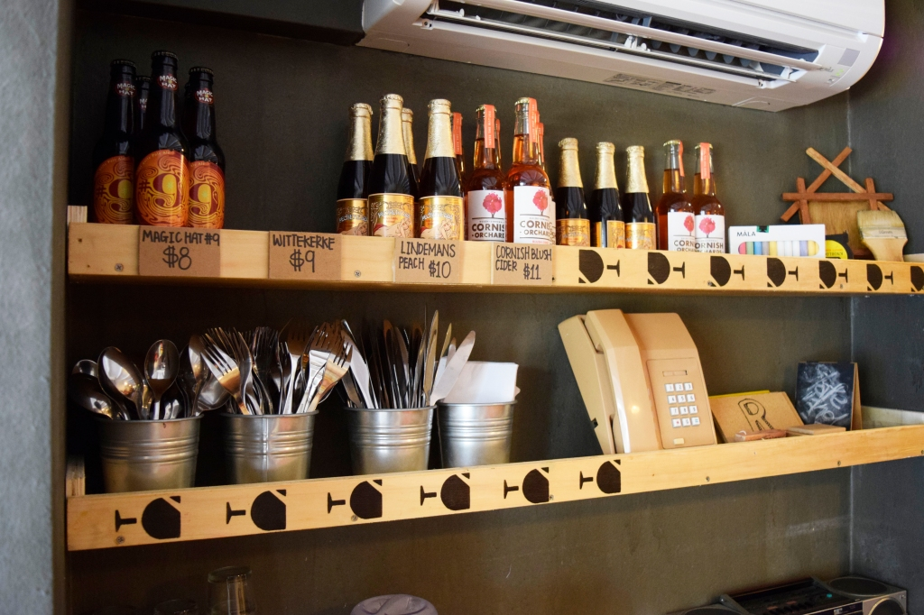 Self-service cutlery and some drinks & knick knacks on display.
