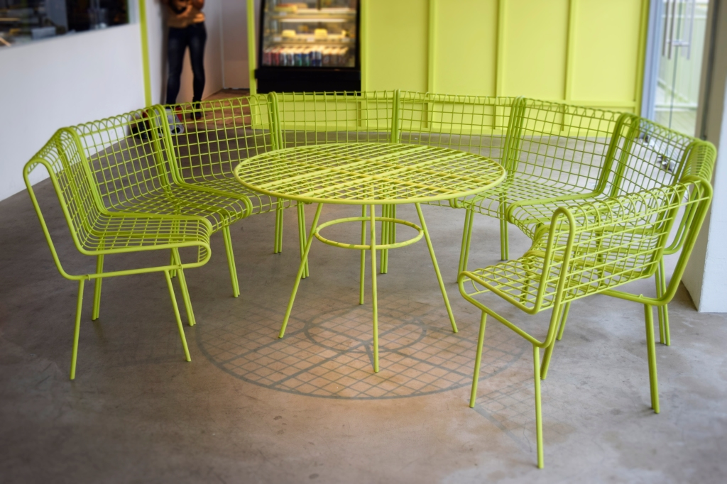 A unique bright green seating area made from metal.