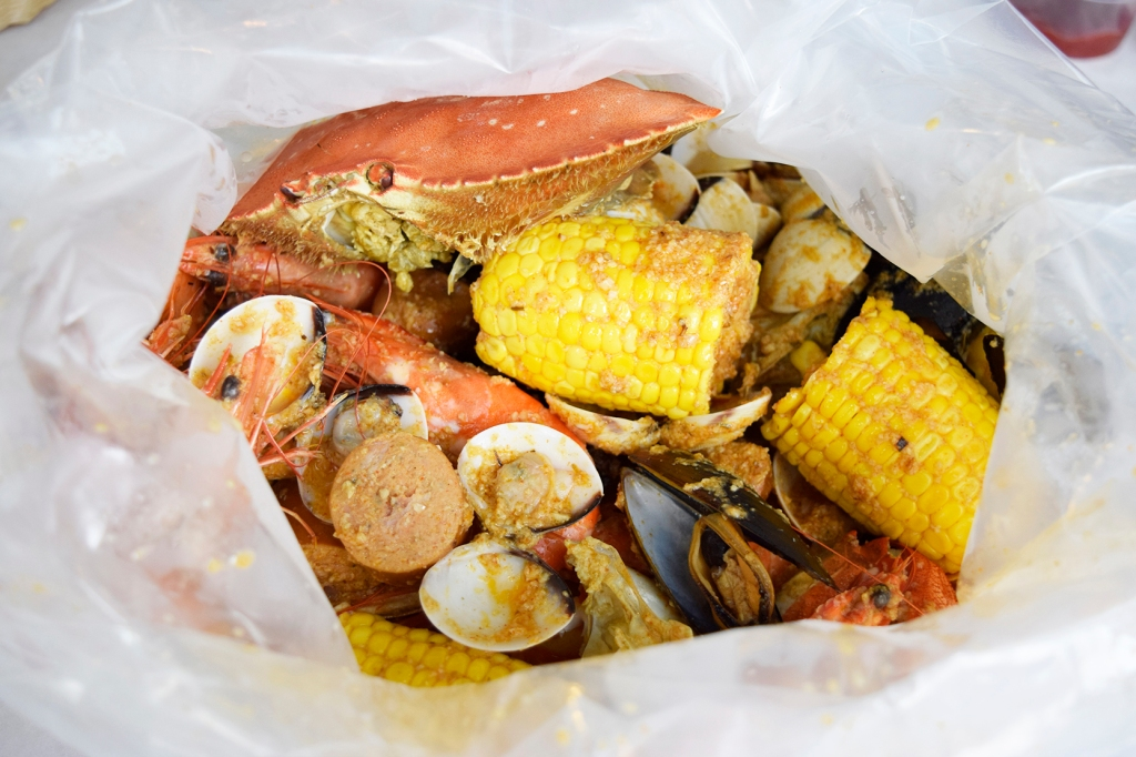 """Boiler's Bombdiggity Bag ($139) Dungeness Crab, Prawns, Clams, Mussels, Sausages, Corn & Fried Buns (Not shown here) Ding! Ding! Ding! Here we have hit the jackpot! Look at all that glorious seafood! This Bombdiggity Bag is actually slated to be for four people, which I found to be more of an estimate/exaggeration. This was shared between my companion & I. Yup... TWO people. (Do bear in mind that I tend to be a big eater, especially when I save myself up for awesome food like this.) I went with a mild version of """"The Works"""" as I'm not a fan of spicy foods."""
