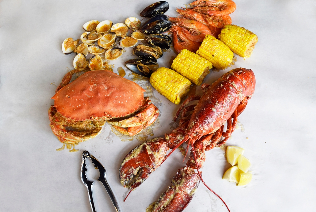 """The contents of the Bombdiggity Bag laid out, along with the Boston lobster. (So pretty.) As you can see, the bag comes with a Dungeness crab, clams, mussels, prawns, corn & sausages. Don't worry, there's more in the bag, I just took some of it out for photography purposes. I'll like to note that both sauces; """"The Works"""" & the Peppa' Butter sauce, seems to have a huge amount of garlic added. It starts to get more apparent once the sauces evaporate, leaving behind chunks of garlic. It does add flavour to the sauces, but the taste of it is also pretty strong. (It even lingered in my mouth till the next day.) Perhaps a smaller amount of it would make the sauces perfect. I'll also like to note that the lobster here seemed bigger than the one I had at The Cajun Kings while the crab I had over there seemed bigger than the one I had here. The downside to this is that as they are fixed pricing, you won't know what you'll be getting, big or small."""