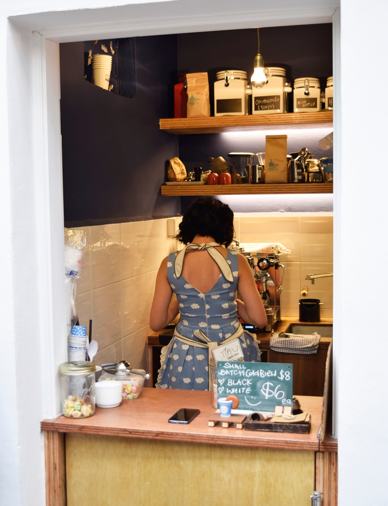 One of the owners of the place, who works as the barista of the cafe in this tiny nook.