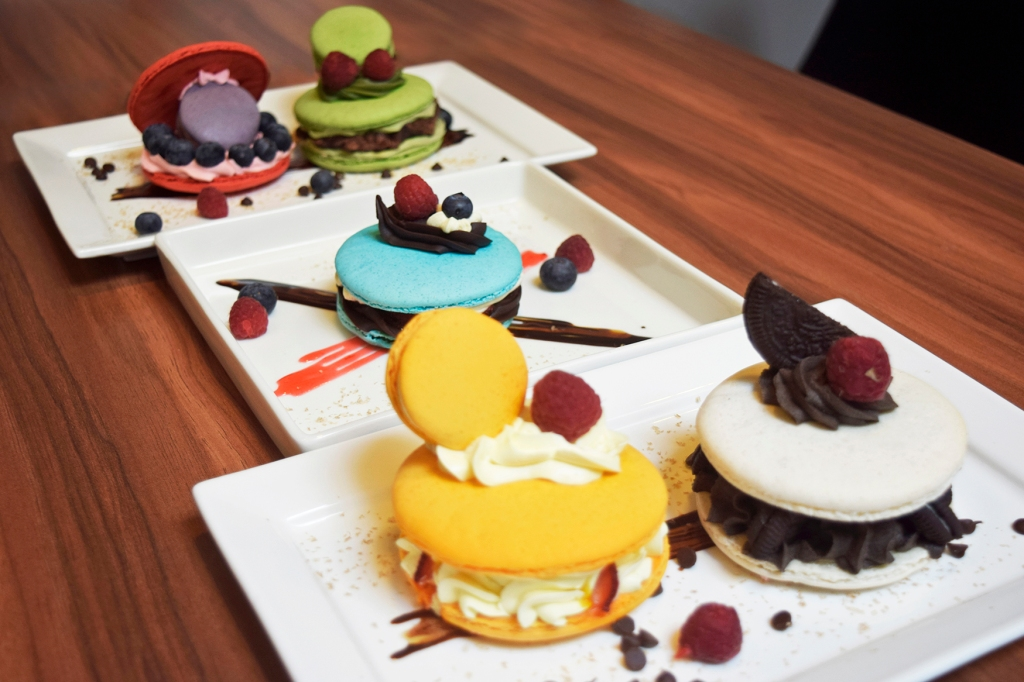 """3 Inch Macarons by Macarcons.sg ($7.90 each) Cheesy Oreo, Matcha Azuki, Mango Passion, Neapolitan, Berry Surprise Finally, these bad boys were available on my second visit. Having failed to try them on my first, I was like """"Heck, I'll just get them ALL."""" And that was what I did. Do bear in mind it was only to be shared between my friend & I. Yes, two people. (Ended up packing most of them up for takeaway - Perhaps my signature move.) I've previously had a giant macaron a while back by some other bakery & that was horrid. I came to the conclusion that macarons simply could not be too big as they would lose their shell texture. I was proven wrong when I tried Macarons.sg's variations.  They were awesome. Each had a distinct flavor & color that were just absolutely pleasing.  You can even see that some of them have a normal sized macaron to go along with it! (A macaron within a macaron; Inception.) The giant shells still retained the iconic macaron texture; crisp on the outside, soft on the inside. The accompanying creams for each macaron was also fantastic. A definite must to try, especially if you are a lover of macarons."""