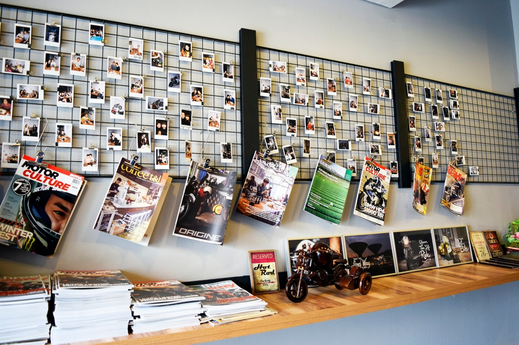 Stacks of magazines of motorcycles & a neat metal wall rack filled with Polaroids.