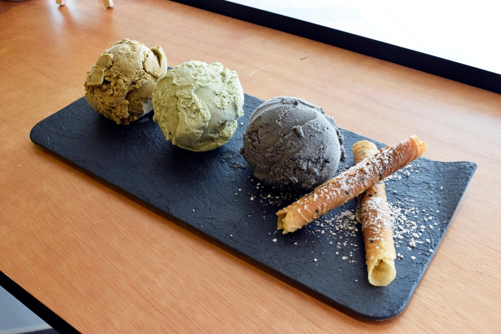 "Ice-Cream Platter ($9) Earl Grey, Happy Pistachio & Roasted Black Sesame Being my normal foodie self, I originally wanted to add FOUR scoops of ice-cream onto a waffle. Alena recommended that I get the ice-cream platter instead, since four scoops was probably too much to put onto the waffles. Having seen their pistachio & black sesame flavors on Instagram, I decided to order those two. I chose Earl Grey for the last flavor as I'm currently in sort of an ""Earl Grey"" phase. All three ice-creams looked fantastic beside one another, with neutral pastel colours & two love letters at the side. The flavors for all three were awesome as well. My friend commented that the Earl Grey kinda had a similar taste to Matcha, perhaps due to both being more tea-flavors."