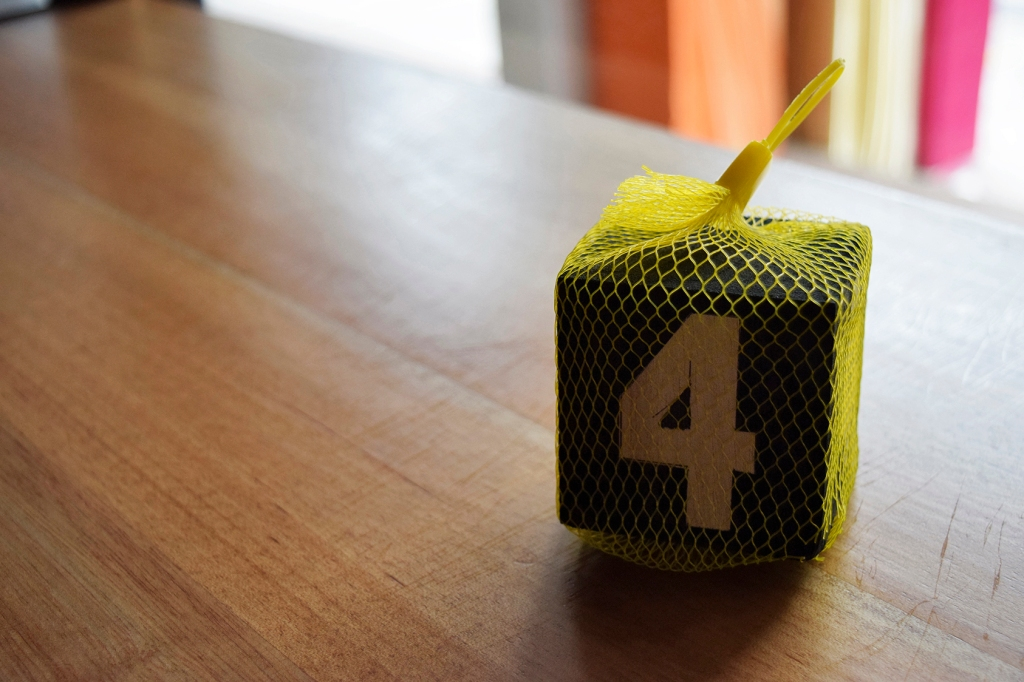 Cool wooden block in netting serves as your table number.